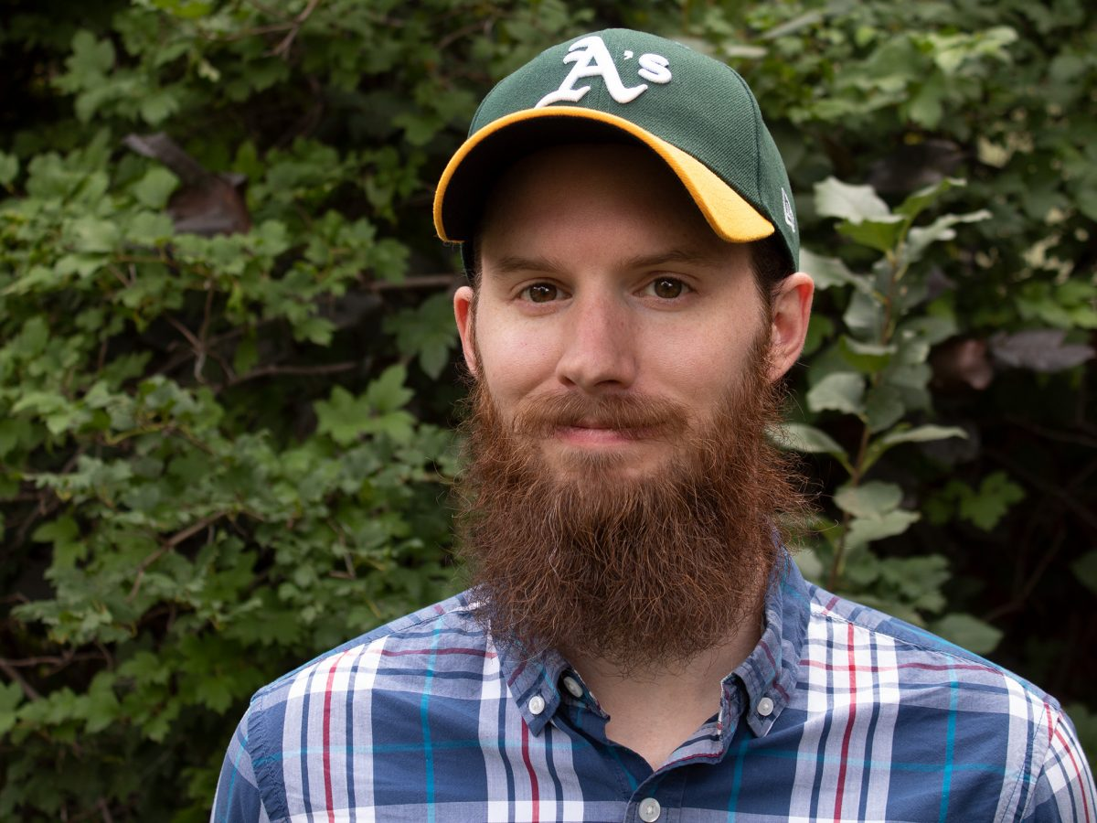 Ron Stauffer with a large beard, smiling at the camera and wearing an Oakland Athletic's ballcap standing in front of a bush.
